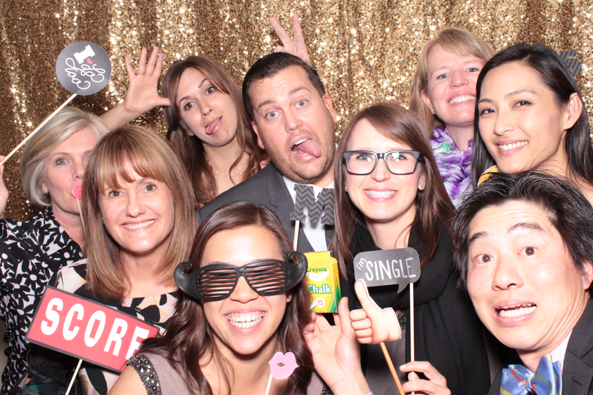 a photo of many wedding guests in a photo booth with a gold sequin backdrop