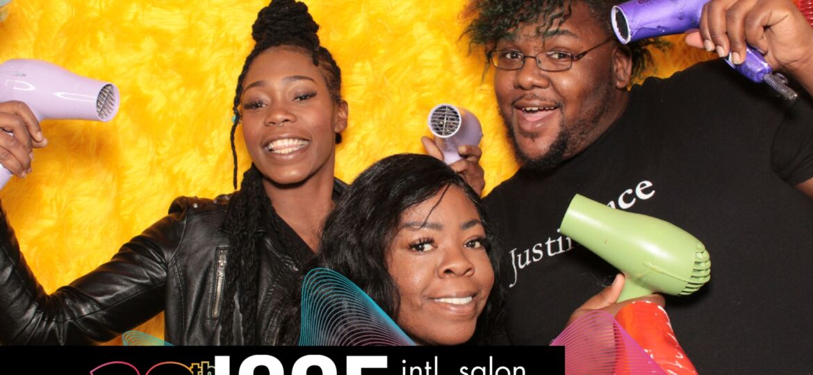 a photo booth photo with 3 guests taken on a yellow backdrop at the International Salon and Spa Expo 2019. Photo taken by photo booth los angeles rental company Maple Leaf Photo Booths